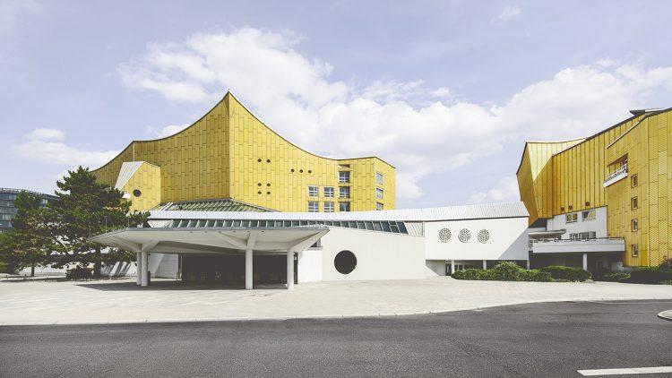 Modernes Gebäude der Berliner Philharmonie mit gelben Aluplatten verkleidet und weißer Eingangsbereich unter blauem Himmel
