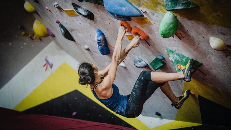 Junge, brünette Frau hängt an Boulderwand und klettert. .