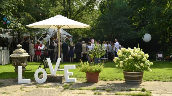 Hochzeitsgesellschaft vor kleiner Kapelle im Grünen