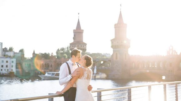 Brautpaar steht auf Terrasse und küsst sich vor Kulisse der Oberbaumbrücke.