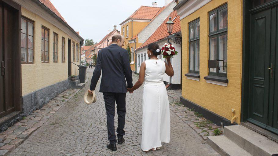 Hochzeitspaar von hinten in enger Straße mit Kopfsteinpflaster und kleinen Häusern