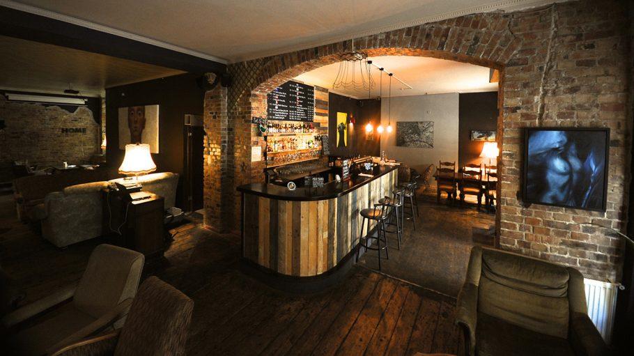 Bar mit Holz und Sesseln und Stuck an Decke