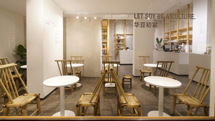 Sitzbereich im Huadou. Kleine weiße runde Tische und Bambusstühle.