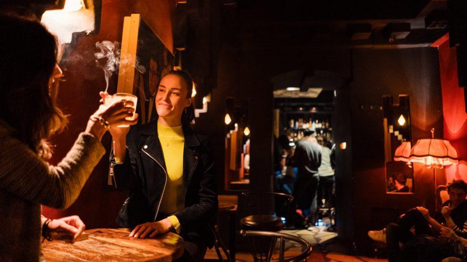 Bar mit kleinen Tischen, im Vordergrund prosten sich zwei junge Frauen zu, im Hintergrund Theke mit Leuten zu sehen