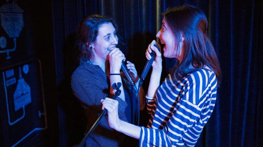 Karaoke zwei Sängerinnen mit Mikrofonen