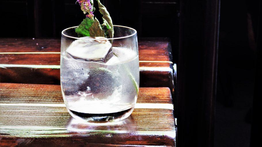 Ein Drink auf Holztisch mit blühender Minze.