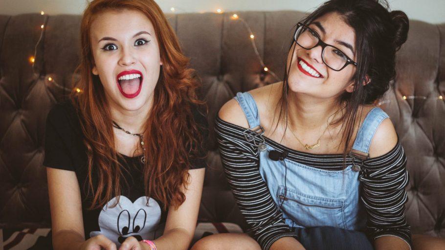 Mädchen sitzen zusammen auf der Couch und haben Spaß.
