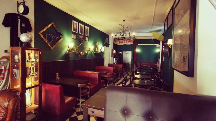 Bar mit roten Ledersesseln, einem Kronleuchter und viel Platz.