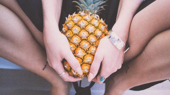 Frau kniet und hält eine Ananas in der Hand.