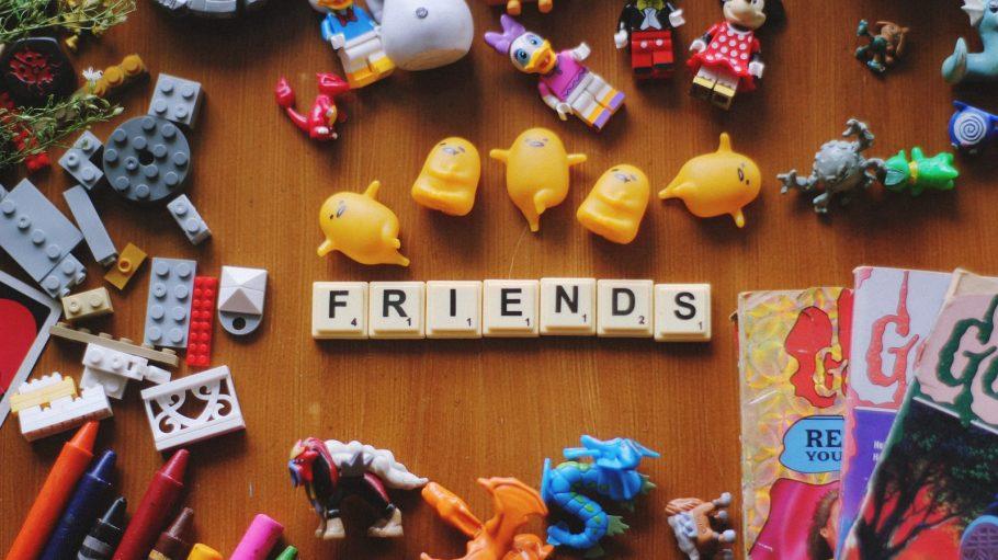 Spielzeug und Malsachen liegen auf dem Boden. Buchstaben bilden das englische Wort Friends.