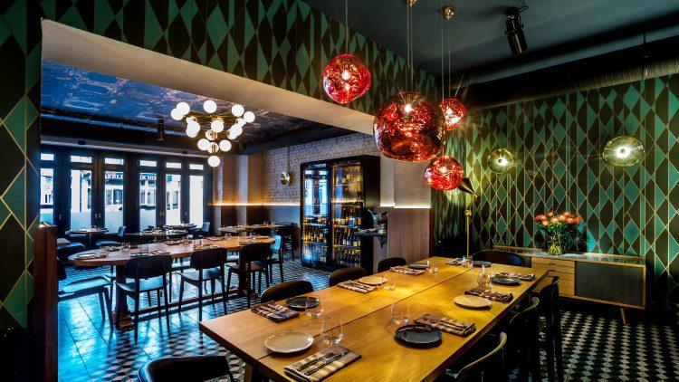 Restaurant mit großem Holztisch und roten Lampen.