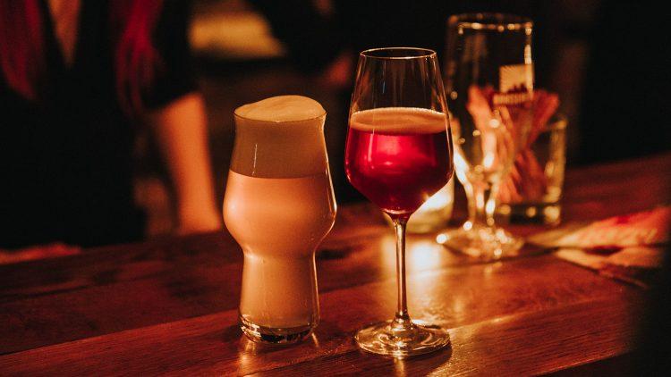 Zwei unterschiedliche, gefüllte Biergläser auf Holztresen, im Hintergrund Barpersonal