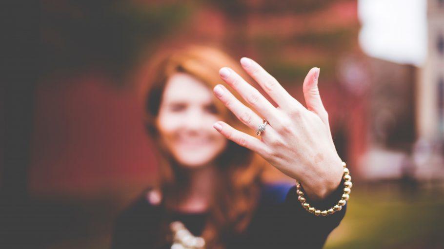 Frau mit roten Haaren hält linke Hand mit Goldring in die Kamera