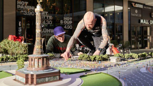 Dr. Motte (lila Baseballkappe, grünes Shirt) und tätowierter Mann mit Punk-Outfit bauen an Modell der Straße des 17. Juni