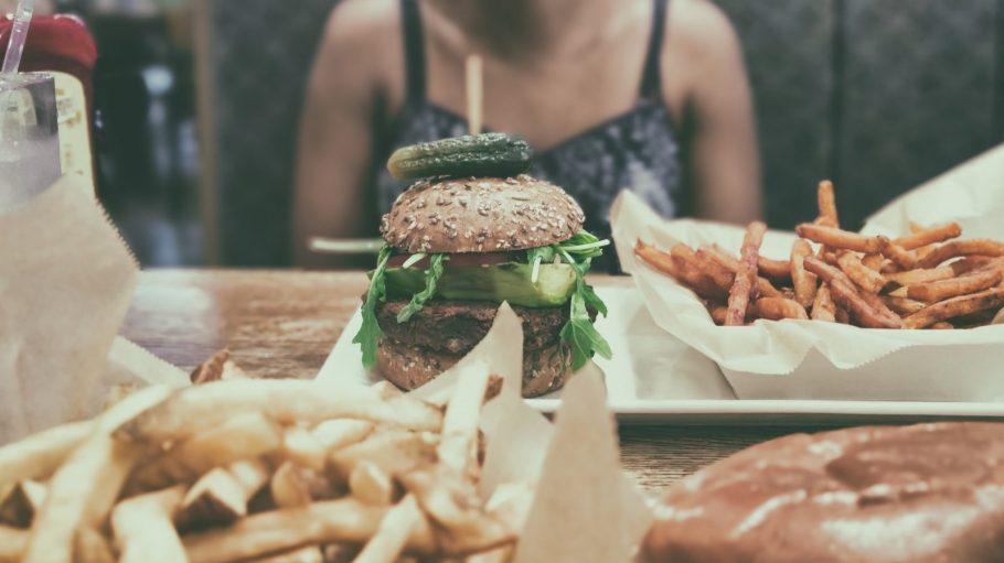 Burger mit Pommes auf Tisch, im Hintergrund Oberkörper einer Frau im Top.