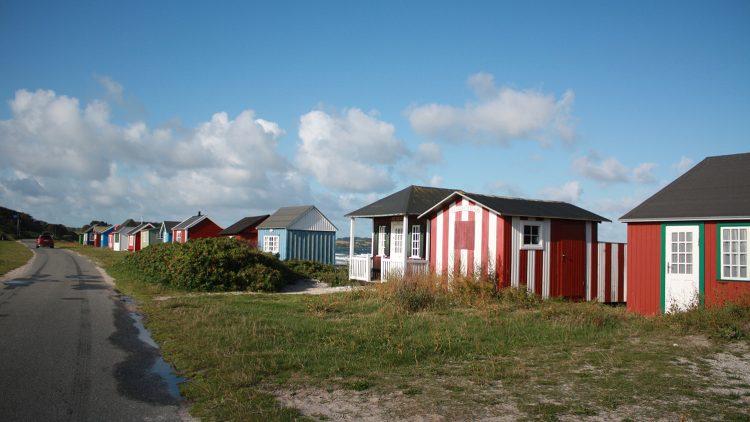 Straße, daneben bunte Strandhäuser unter blauem Himmel, ein bisschen Meer zu sehen