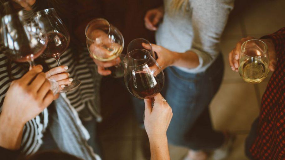 Frauenkörper mit Wein in der Hand, die anstoßen.