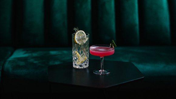Zwei Cocktails auf Tisch, dahinter Samtbank