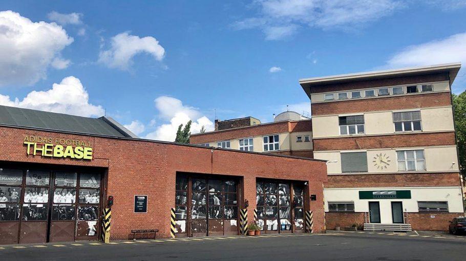 Werkstatt aus rotem Backstein mit geschlossenen Toren von außen, daneben weiß-brauner Gewerbebau mit Uhr, blauer Himmel: Uferhallen Wedding