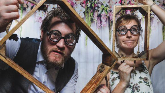 Mann und Frau mit Brille und Holzbilderrahmen in den Händen