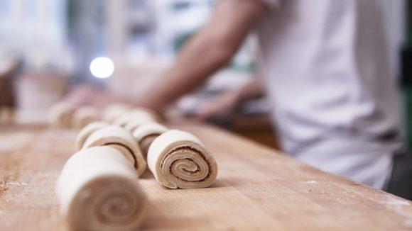 Bäckermeister mit Teigrollen auf dem Tisch - Bäckerhandwerk