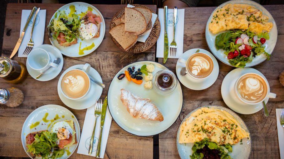 Frühstückstische aus Holz, mit fünf Tellern mit Eierspeisen, Salat, Lachs, Croissant, Tassen mit verziertem Kaffee
