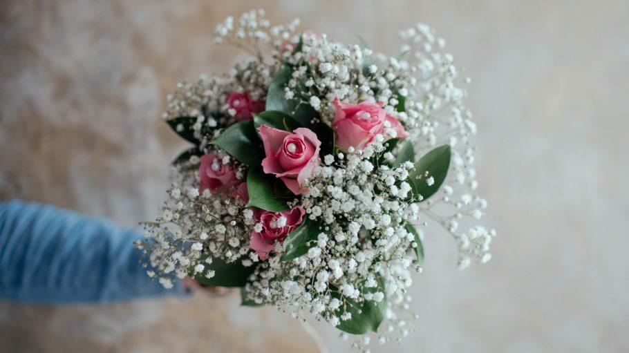 Ein Blumenstrauß mit Rosen und weißen Blumen.