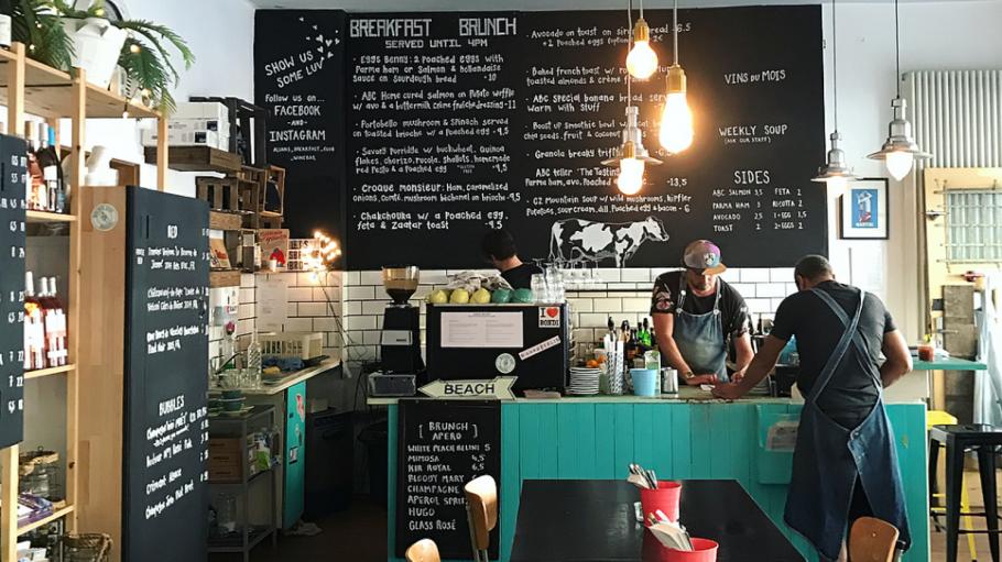 Innenraum von Allans Breakfast Club mit Tresen, Speisekarte auf Tafel, zwei Männer