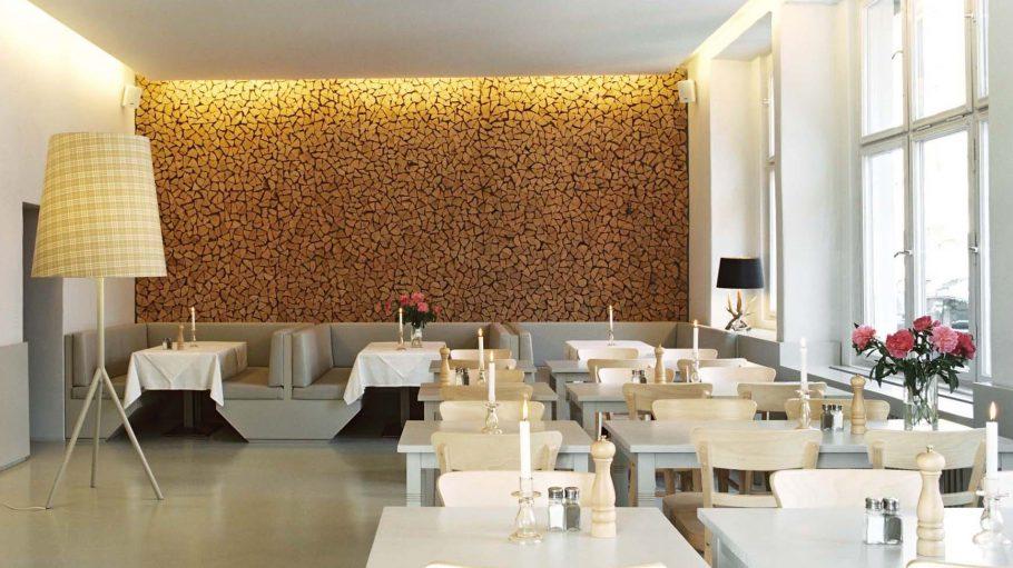 Restaurant mit weißen Tischen und Sitzmöbeln, Wand mit Holzscheiten als Motiv