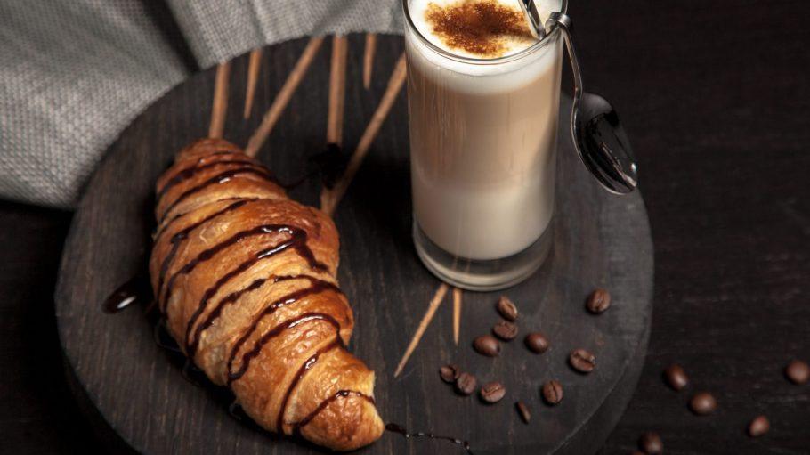Croissant mit Schokosoße und Cafe Latte im Glas mit Löffel