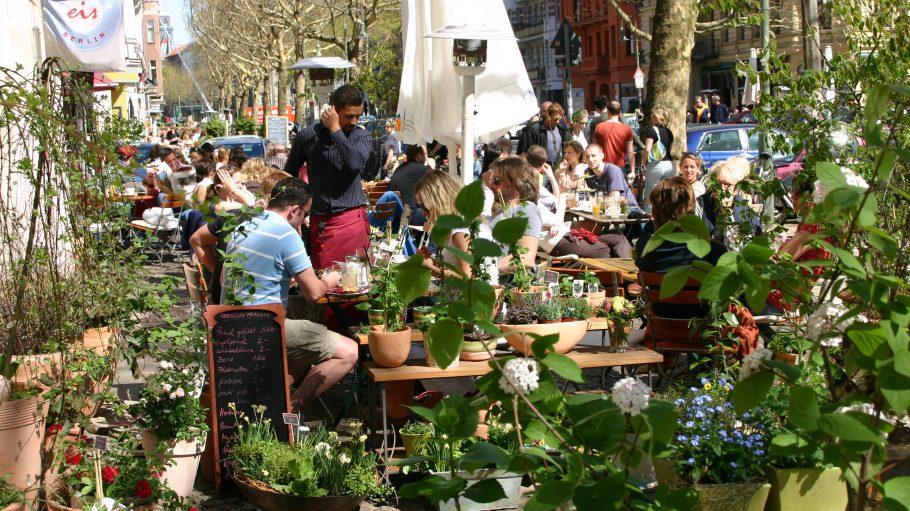 Terrasse von einem Café draußen mit vielen besetzten Tischen und Pflanzen im Vordergrund