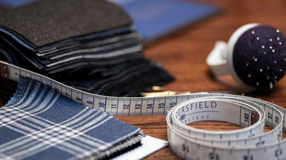 Maßband und Stoffe für einen Anzug auf dem Tisch