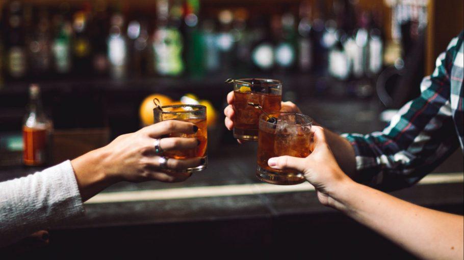 Drei Menschenarme die mit Getränk anstoßen