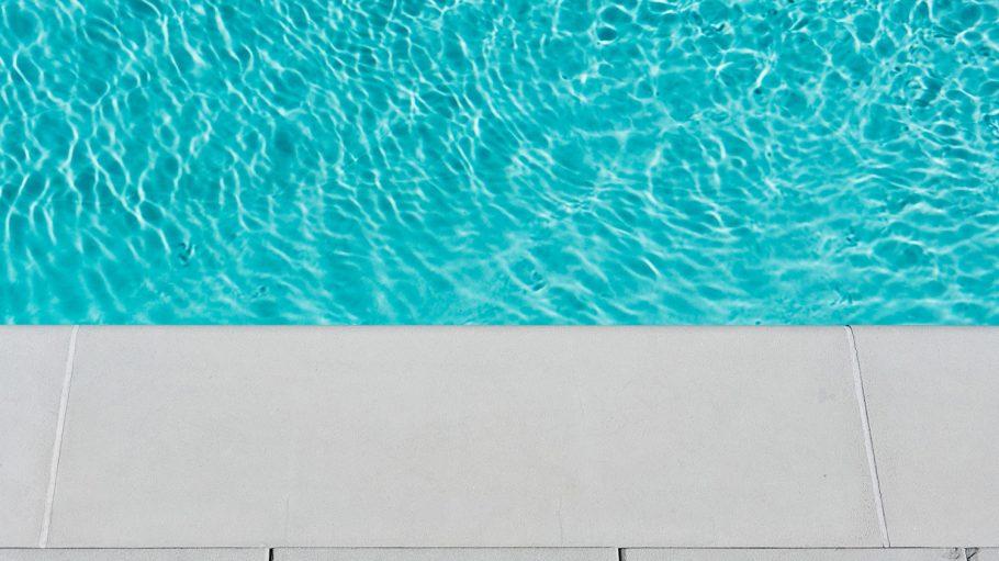 Blau schillerndes Wasser in Schwimmbecken, unten grauer Beckenrand
