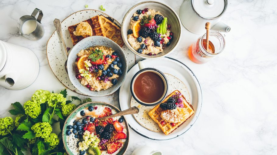 Frühstückstisch mit Obstsalat, Porridge, Teller mit Kaffee und Waffel, Honig, Kanne und Blume