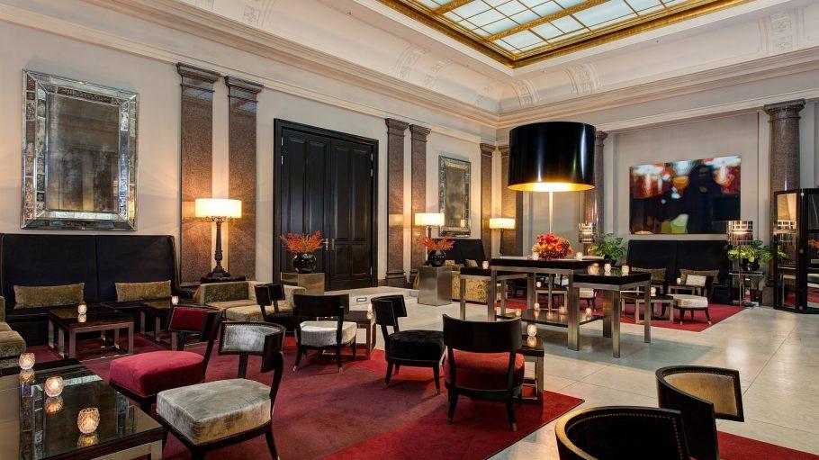 Saal mit roten Teppichen, edlen Stühlen und Tischen, Holztüren