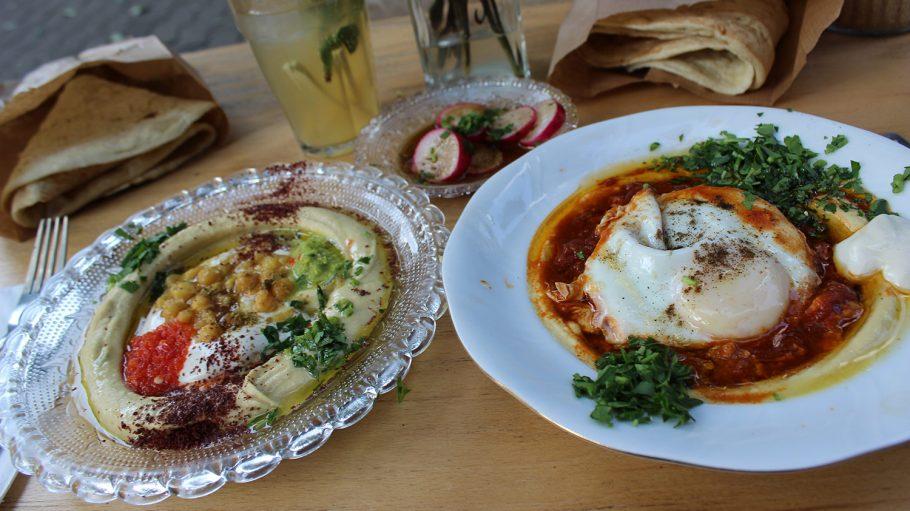 Zwei Teller mit Hummus und Beilagen, dahinter Radieschen und Getränk