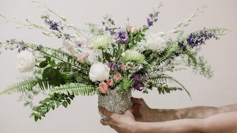Zwei Hände halten Blumenstrauß in die Kamera.