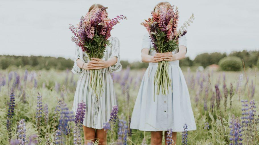 Zwei Frauen stehen auf einer Wiese und halten einen Blumenstrauß in die Höhe.