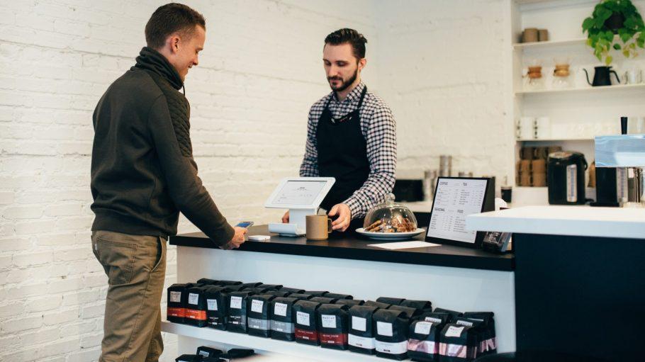 Mann bezahlt Kaffee mit dem Smartphone
