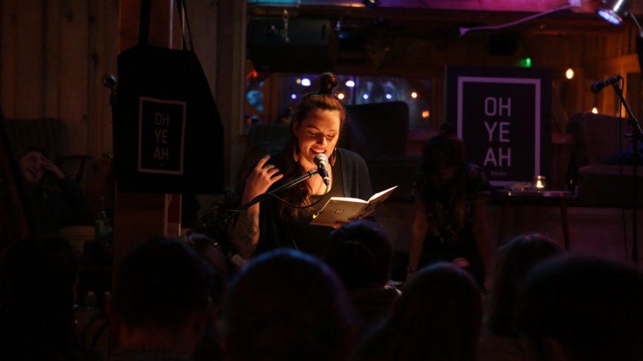 Junge Frau liest vor Publikum aus einem Tagebuch, mit Mikrofon