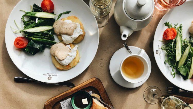 Frühstück: Teller mit Gemüse und Teigwaren, Kanne und Tasse Tee