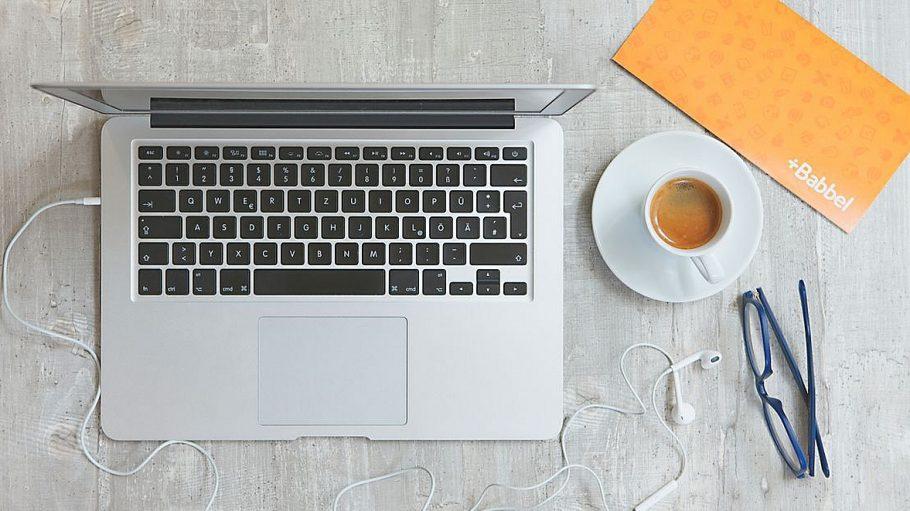 Grauer Laptop, Tasse Kaffee, Brille auf grauem Tisch, Babbel-Karte