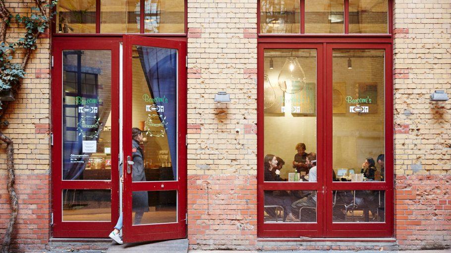 Café mit Backsteinwand von außen und rot lackierter Tür und Fensterrahmen