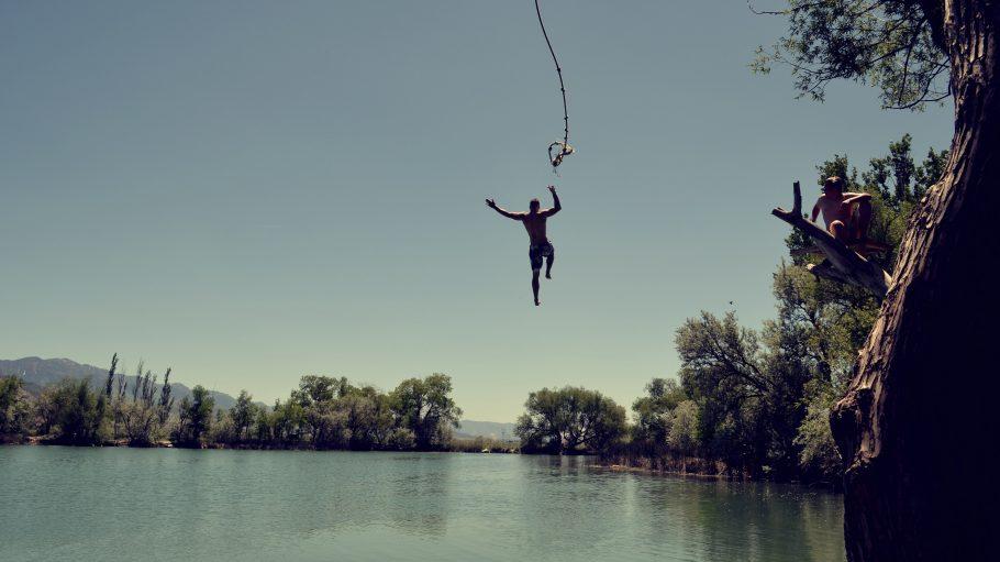 Mann springt mit Seil ins Wasser