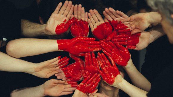 Viele Hände, auf ihnen ein Herz mit roter Farbe