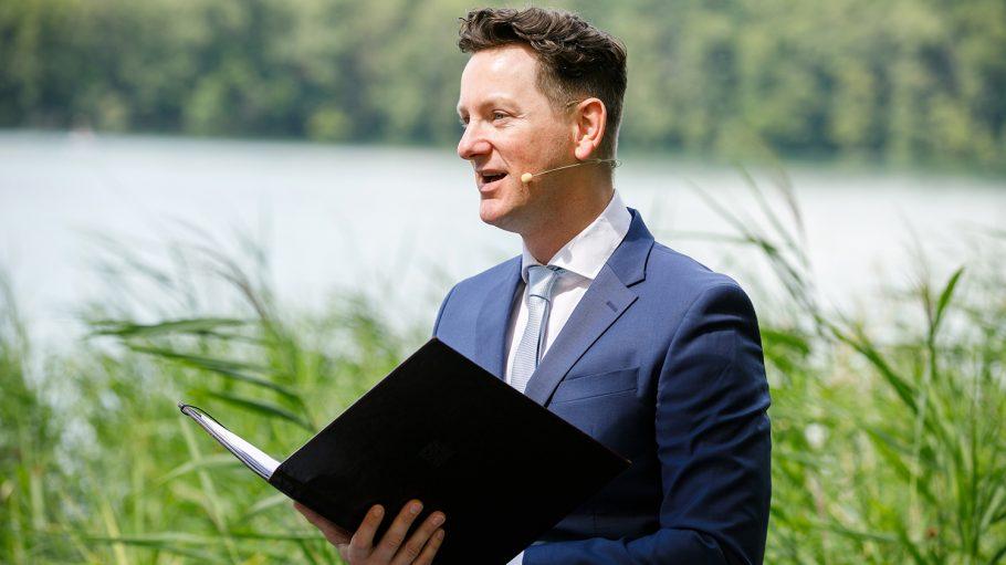 Mann im Anzug und mit kleinem Mikro trägt Traurede aus schwarzer Mappe vor, Hintergrund Gras und See
