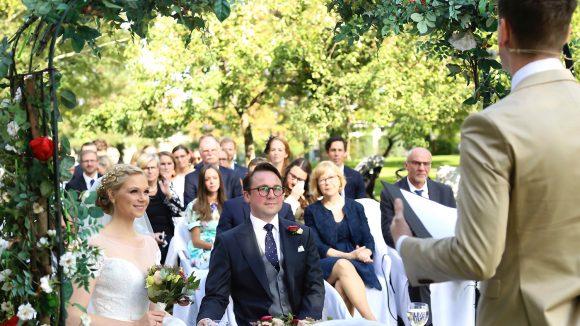 Braut und Bräutigam znd Hochzeitsgesellschaft im Garten lauschen Rede von Trauredner Daniel Pabst, von hinten zu sehen