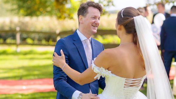 Trauredner im blauen Anzug mit Hemd und Krawatte mit Braut im weißen Kleid, dahinter Park