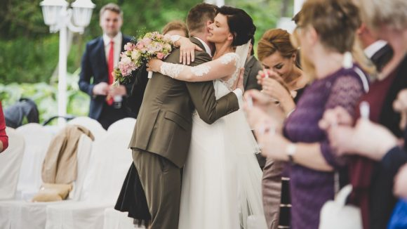 Hochzeitsgesellschaft im Garten; Trauredner im oliven Anzug umarmt Braut